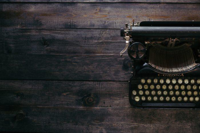 typewriter sitting on a wooden desk